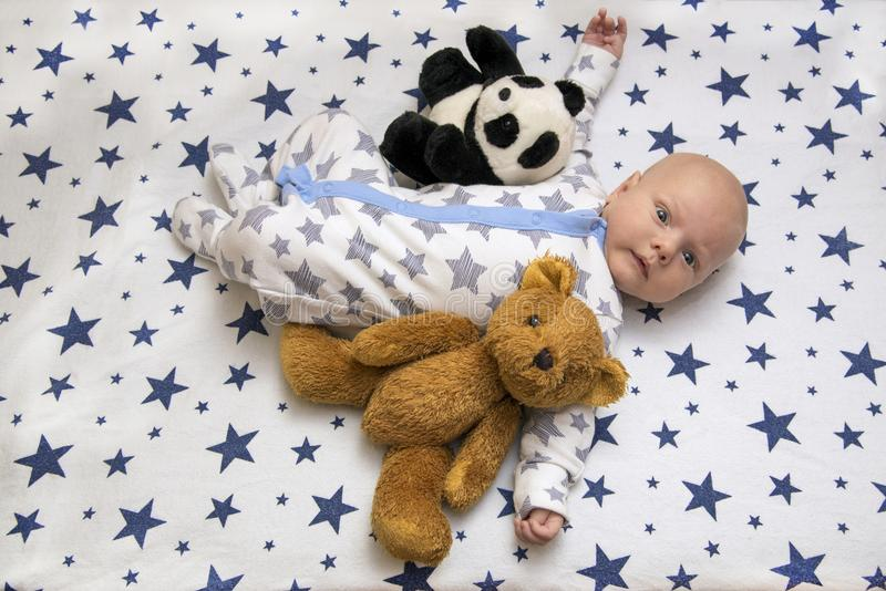 A newborn baby lies in the crib with a teddy bear and a panda, top view. A newborn baby lies in his crib with a teddy bear and a panda, top view royalty free stock photos