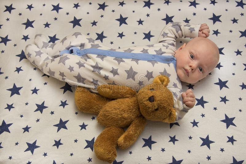 A newborn baby lies in the crib with a teddy bear, top view. A newborn baby lies in his crib with a teddy bear, top view royalty free stock images