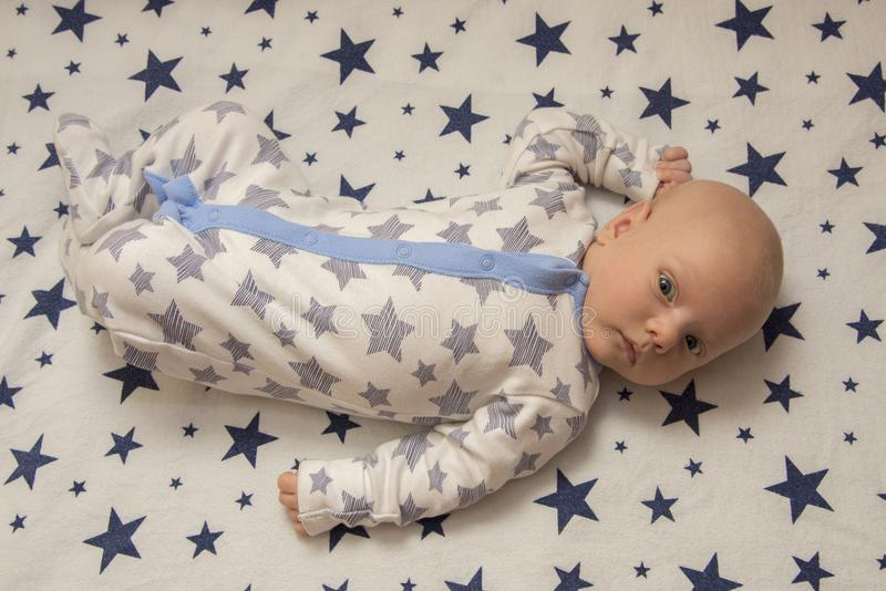 A newborn baby lies in the crib, top view stock images