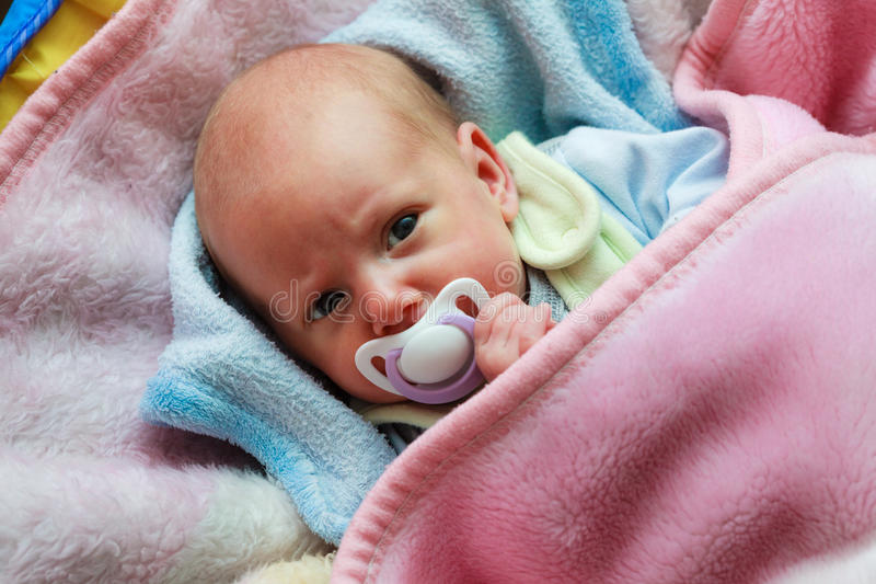 Newborn baby lying in bed with dummy stock images