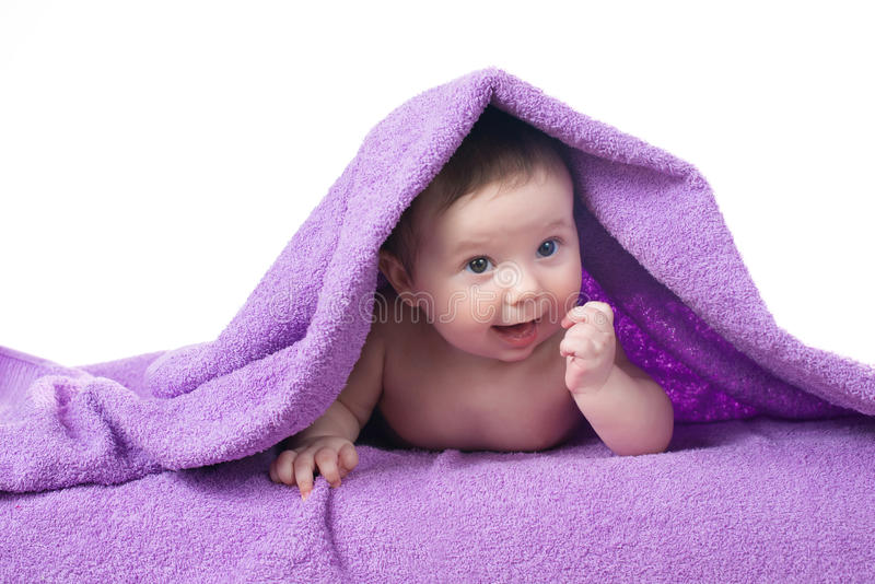 Newborn baby lying down and smiling in a purple towel stock photo