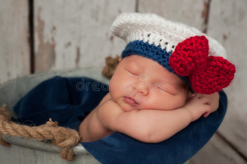 Newborn Baby in Sailor Girl Hat. Eight day old newborn baby girl wearing a white and blue sailor hat with red bow. She is sleeping inside of a galvanized bucket stock image