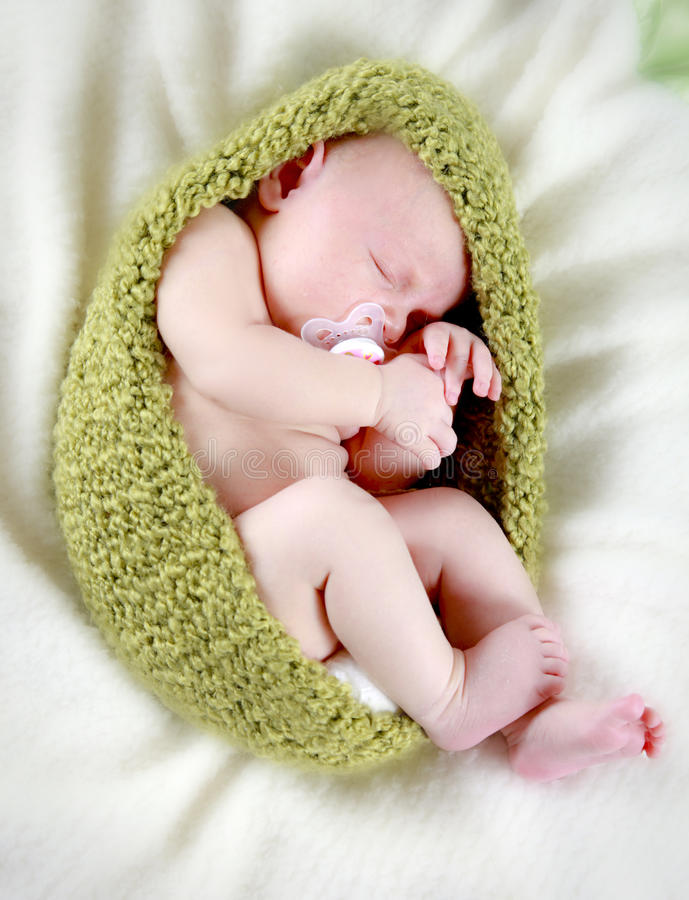 Newborn baby sleeping. A closeup of a tiny, newborn baby sleeping in a knit cocoon or blanket stock images
