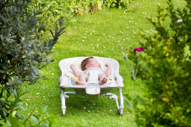 Newborn baby sleeping in a bouncer in the garden royalty free stock images
