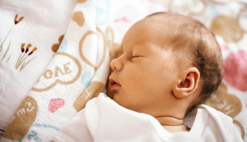 Newborn baby sleeping in the crib on a blanket. The photo has a empty space for your text stock image