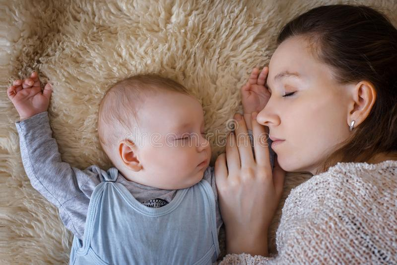 Newborn baby sleeping next to her mother.  royalty free stock photos