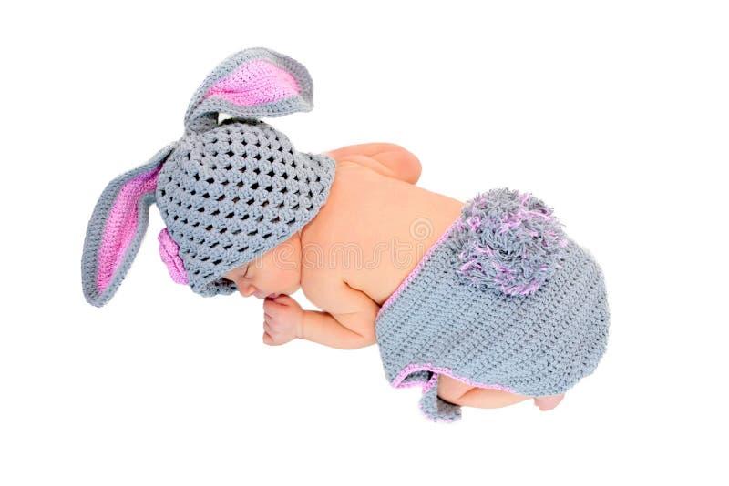 Newborn baby sleeping in rabbit costume. royalty free stock images