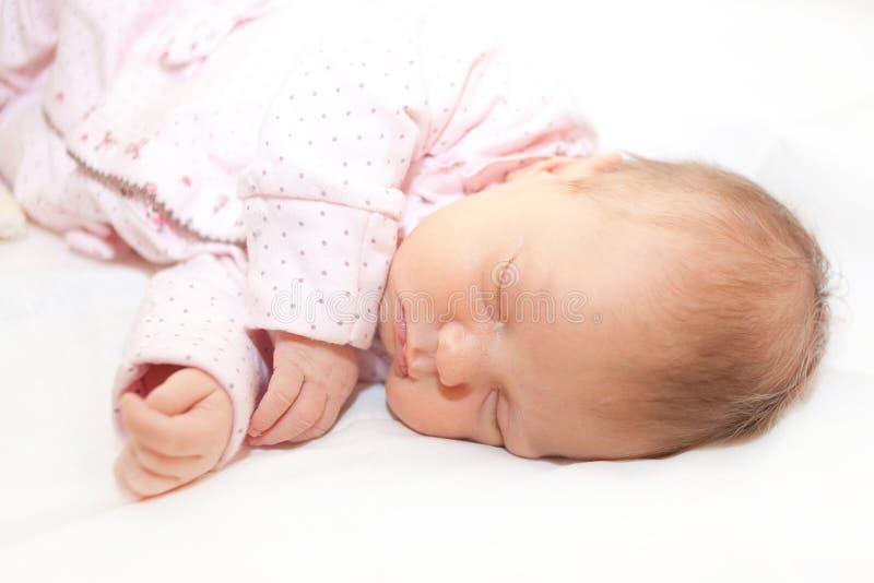 Newborn baby is sleeping on white bed stock image