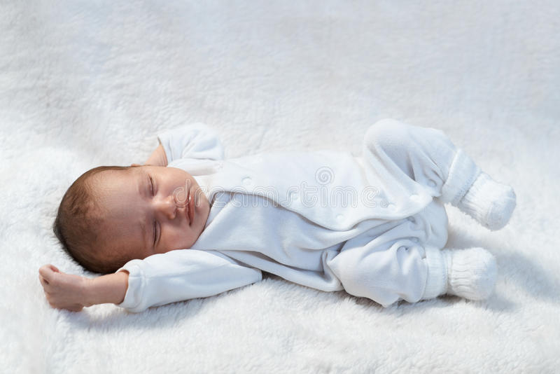 Newborn baby sleeping on white fur in sunlight stock images