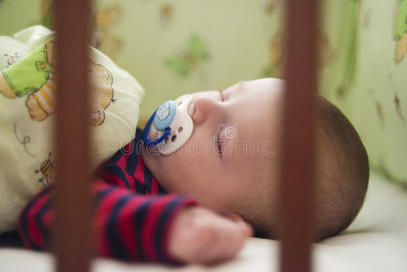 A newborn baby sleeps in his bed. Healthy sleep. Baby lying in the bed with green bedding stock photo