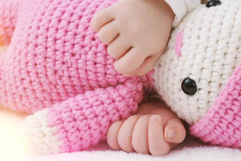Newborn baby sleeps with a pink toy baby and hands hugs stock image