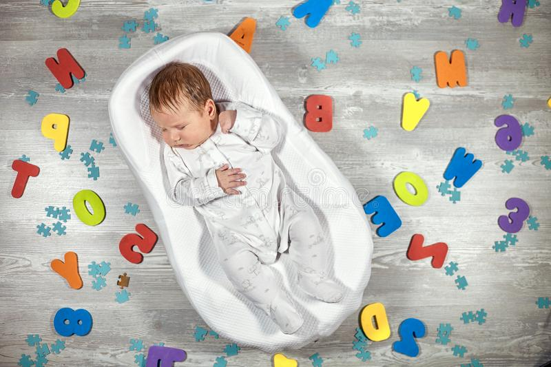 Newborn baby sleeps in a special orthopedic mattress Baby cocoon, on a wooden floor multicolored letters around. Calm royalty free stock photography