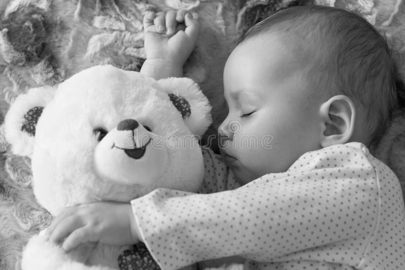 Newborn baby sleeps with a teddy bear black and white royalty free stock images