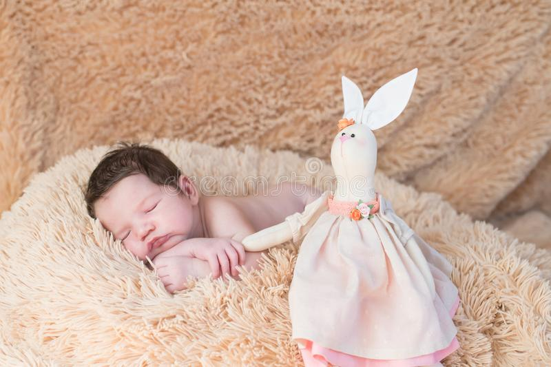 A newborn baby sleeps with a toy, a plush hare. My best friend the baby is sleeping with her teddy kidney on the bed. New family royalty free stock photos