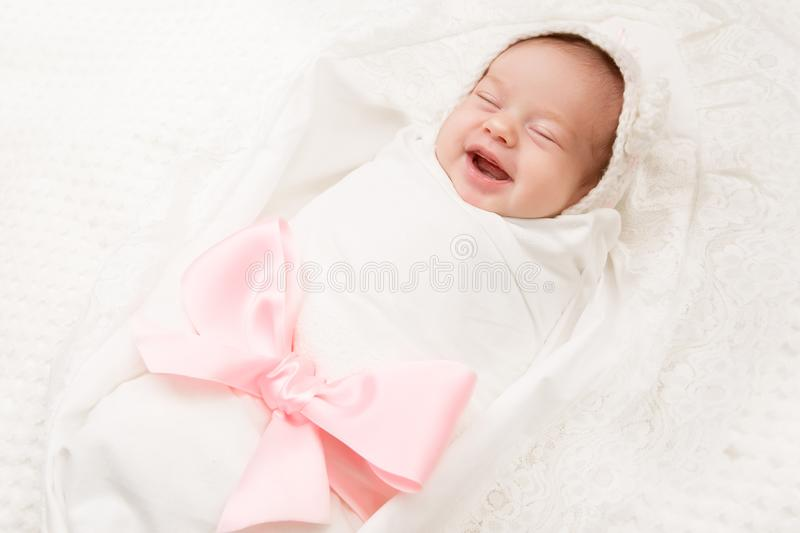 Newborn Baby Smile, New Born Girl Smiling Wrapped by Ribbon Bow. Happy Two Weeks Old Kid on White stock photo