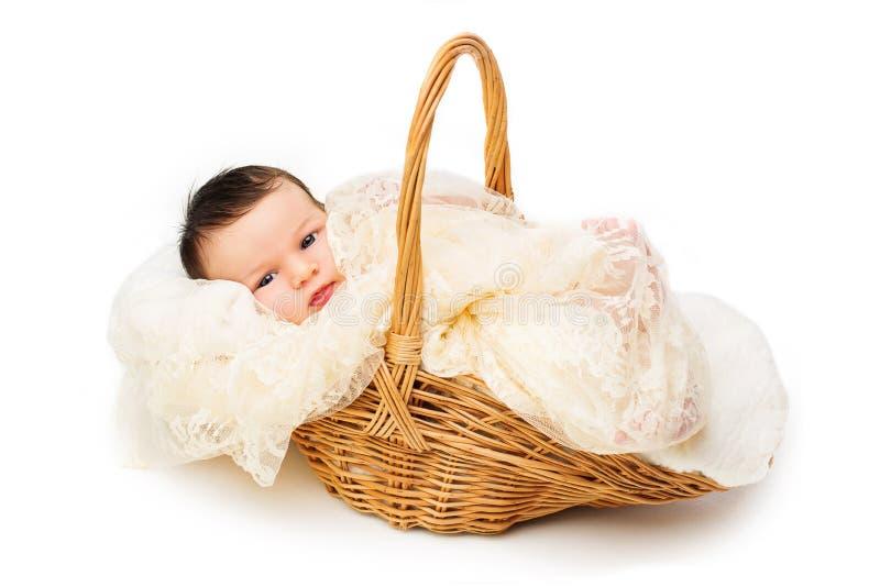 Newborn baby smiling in a wicker basket stock image