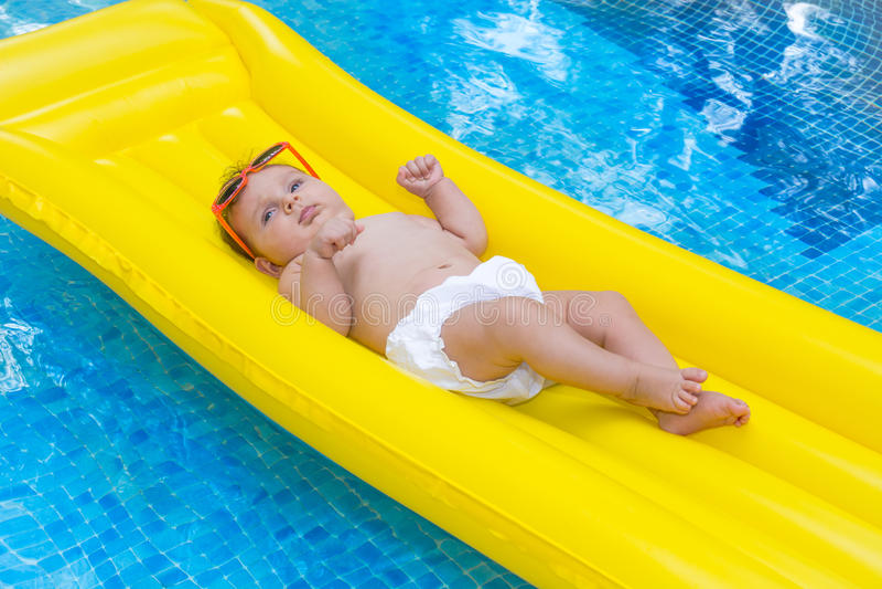 Newborn baby on summer mattress stock images