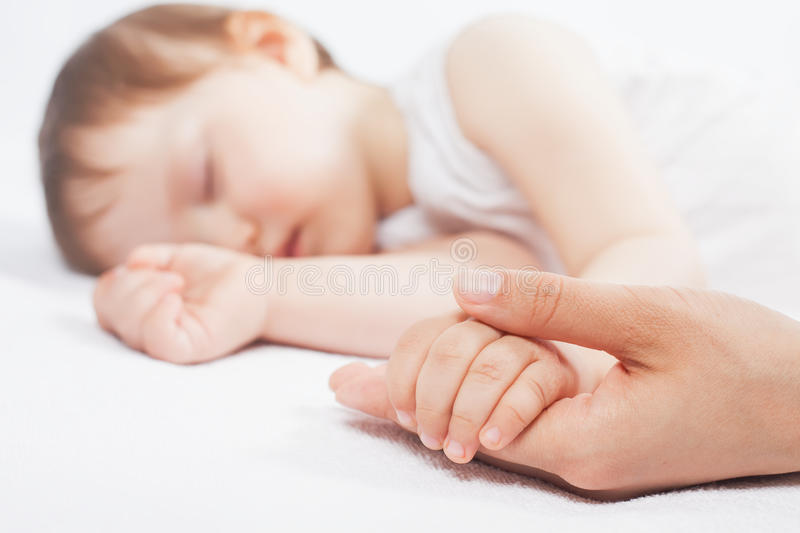 Newborn baby sweet sleeping on a white bed. Newborn baby with mother sweet sleeping and holding hands on a white bed. Comfortable bed. Concept of baby care. Care royalty free stock photos