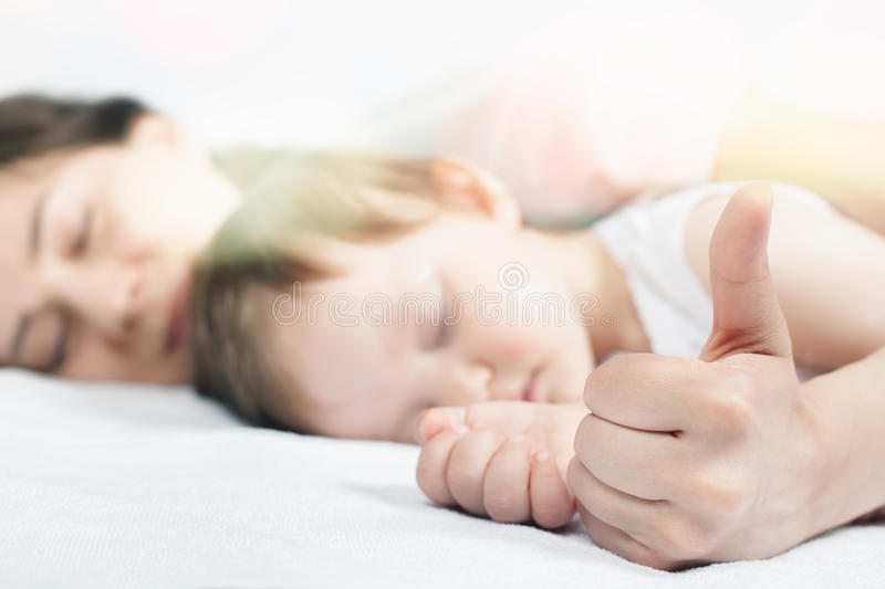 Newborn baby sweet sleeping on a white bed. Newborn baby with mother sweet sleeping and holding hands on a white bed. Comfortable bed. Concept of baby care. Care stock image