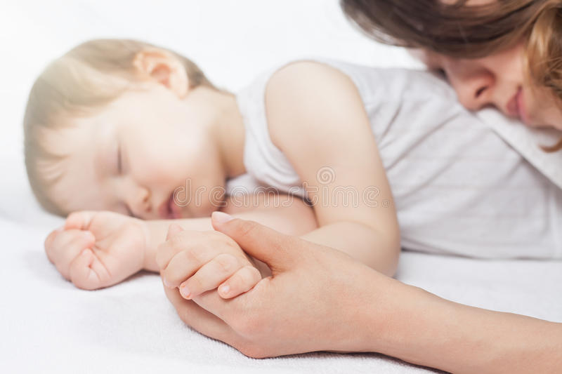 Newborn baby sweet sleeping on a white bed. Newborn baby with mother sweet sleeping and holding hands on a white bed. Comfortable bed. Concept of baby care. Care stock images