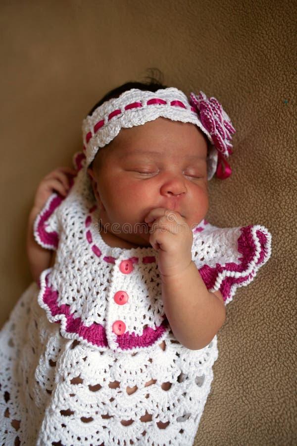 Newborn black baby sucks his thumb. Newborn black baby girl sleeps and sucks her thumb stock images