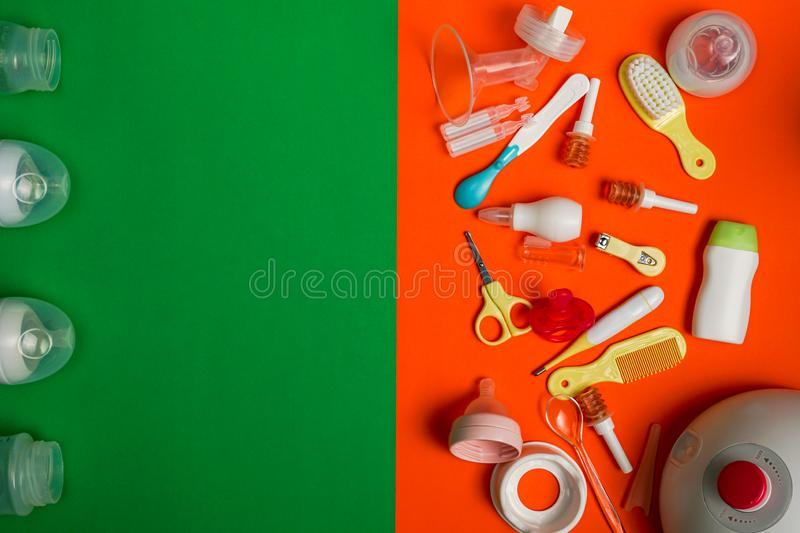Newborn care and breastfeeding accessories on green and orange background royalty free stock photo