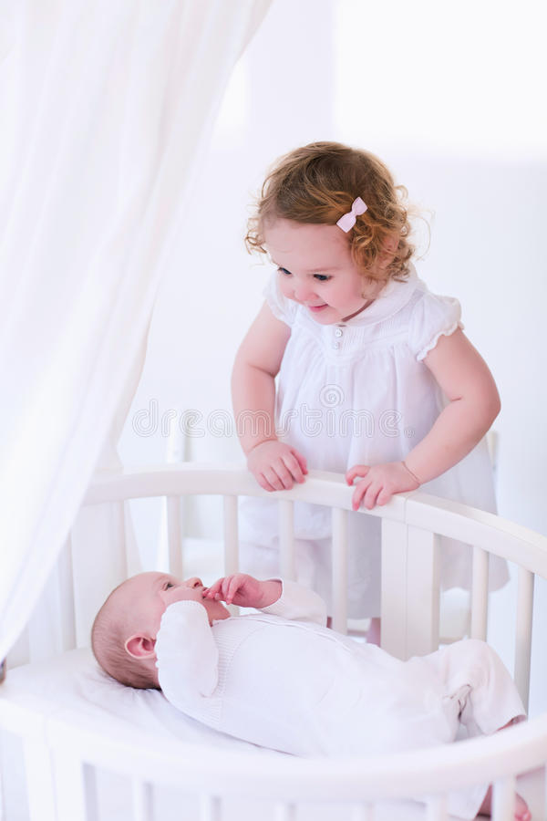 Newborn child meets his sister. Kids in bed. Two children playing together in a white sunny bedroom. Little girl meets her newborn baby brother. Siblings play royalty free stock photo