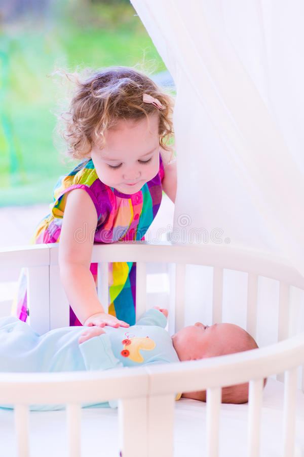 Newborn child meets his sister. Kids in bed. Two children playing together in a white sunny bedroom. Little girl meets her newborn baby brother. Siblings play stock images