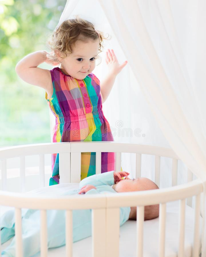 Newborn child meets his sister. Sister and baby brother. Little girl meeting newborn sibling. Kids in bed. Two children playing together in a white sunny bedroom royalty free stock images
