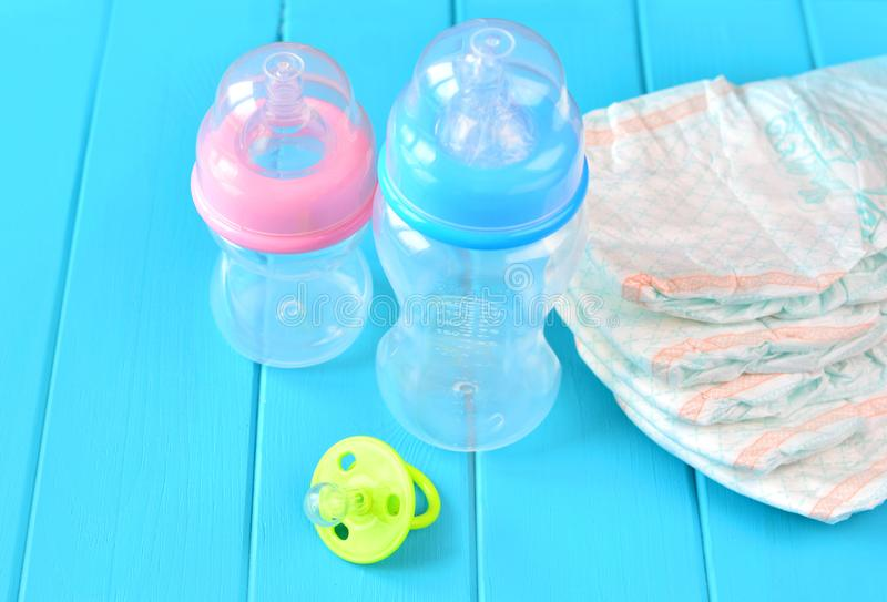 Newborn child stuff on a wooden background. Stack of baby disposable diapers, pacifier and feeding bottles close-up. royalty free stock photo