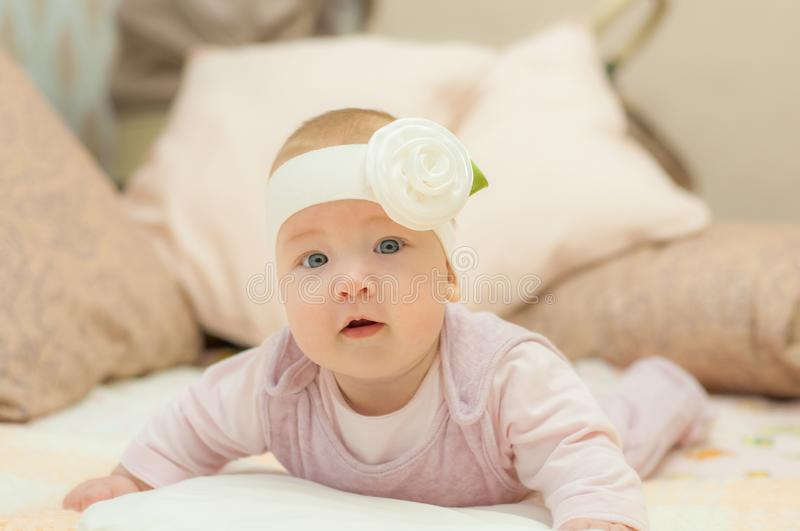 Newborn child wearing a diaper in white sunny bedroom. Newborn child relaxing in bed. Beautiful girl lies a happy smile, great stock photo