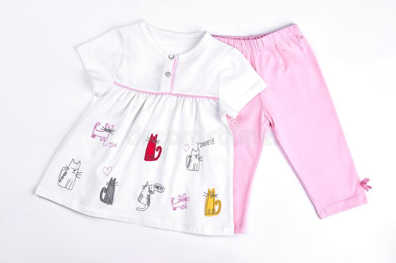 Newborn girl beautiful summer clothes. Infant girl set of white cartoon dress and pink leggings. Baby-girl cute summer garment on sale royalty free stock photos
