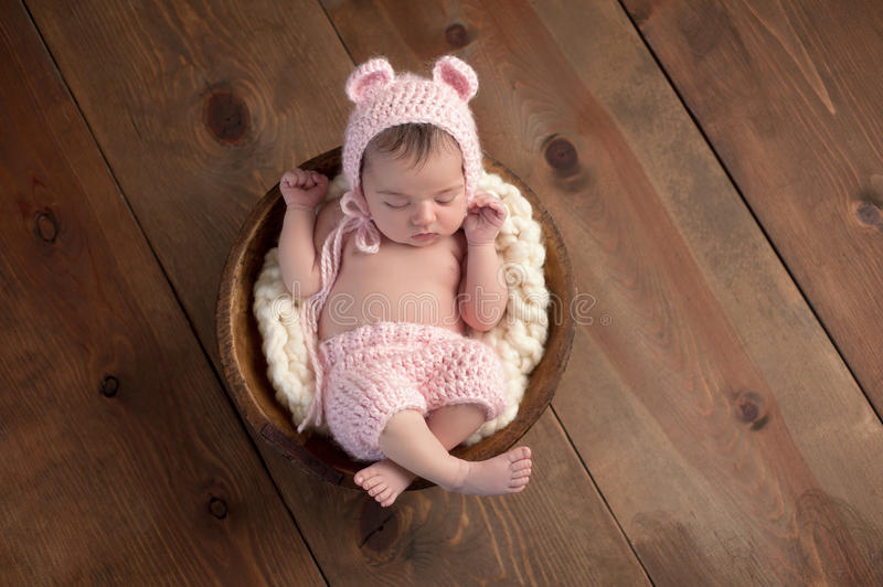 Newborn Girl Wearing a Pink Bear Hat. An overhead shot of a two week old newborn baby girl sleeping in a little, wooden bowl. She is wearing a crocheted, pink stock photos