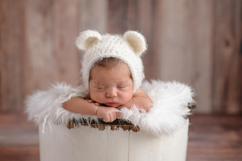 Newborn Girl Wearing a White Bear Hat. An 11 day old newborn baby girl sleeping in a little, wooden bucket. She is wearing a crocheted, white bear bonnet. Shot stock photography