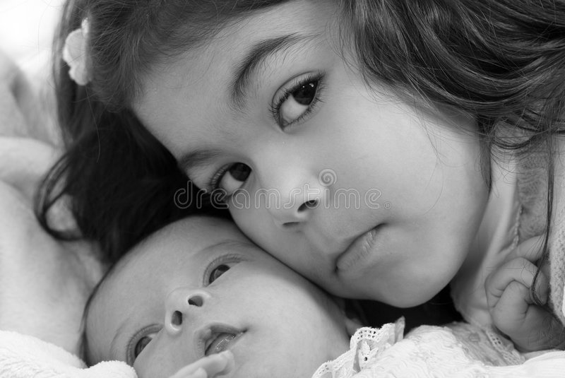 Newborn and sister. A newborn little girl with her big sister. Family, love, caring royalty free stock photography