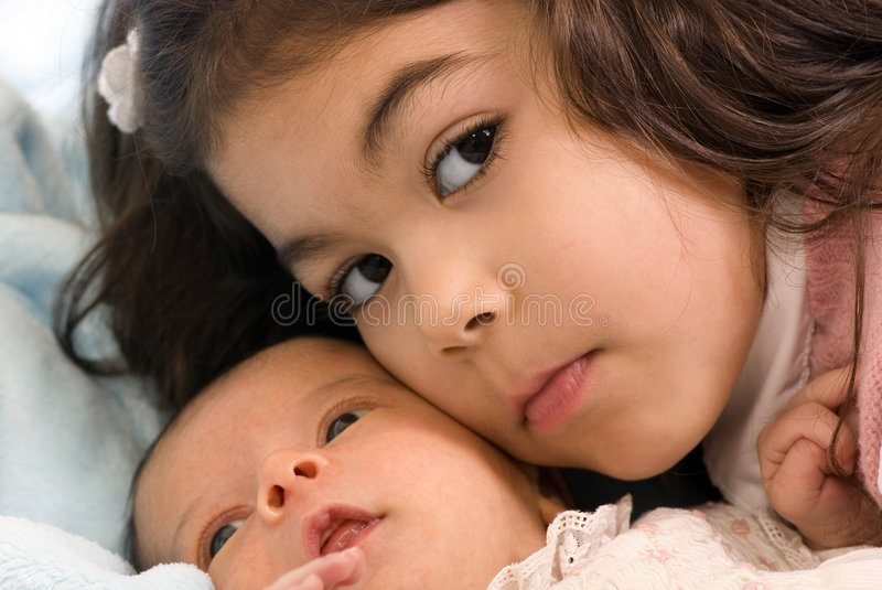 Newborn and sister. A newborn little girl with her big sister. Family, love, caring royalty free stock images