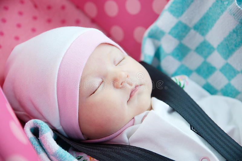 Newborn sleeping in car seat.Safety concept. Infant baby girl. secure driving with children. Baby care lifestyle. Cute baby. Sleeping in car royalty free stock image