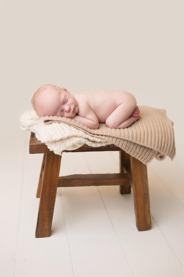 Newborn Sleeping on Chair. Newborn Baby Asleep, sleeping and taking a nap on a rustic wood chair, posed and curled up royalty free stock image