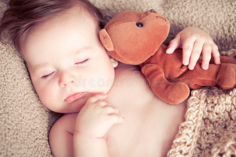 Newborn sleeping with a toy. Newborn baby boy sleeping with a teddy bear toy royalty free stock photo
