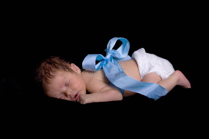 Newborn Wrapped up in Blue Ribbon with Bow stock image