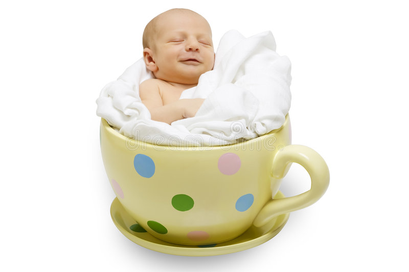 Newborn in yellow cup stock photography