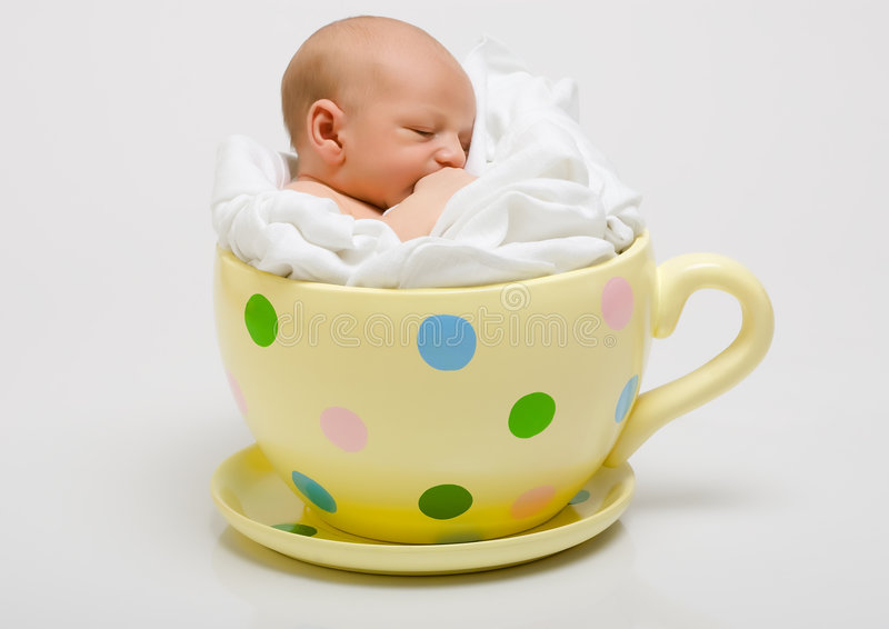 Newborn in a yellow spotted cup stock photos