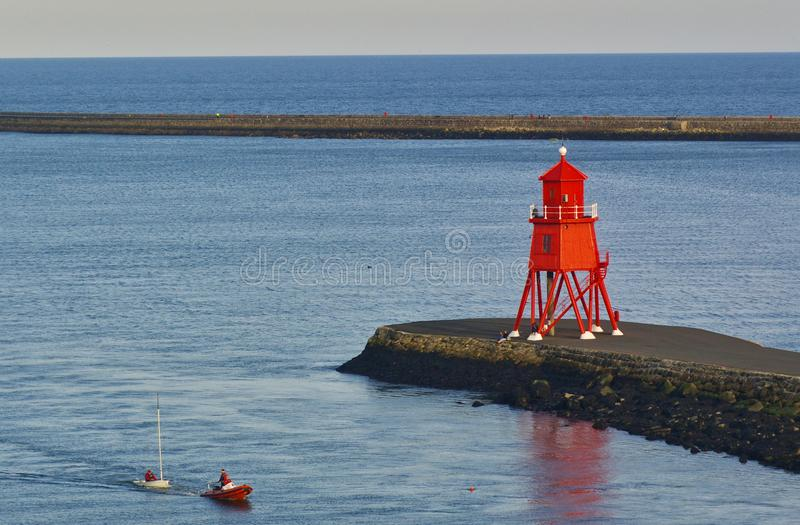 Newcastle, United Kingdom - October 5th, 2014 - Becalmed sailing dinghy in the mouth of the river Tyne is being towed ashore by a. RIB next to a breakwater with stock photos