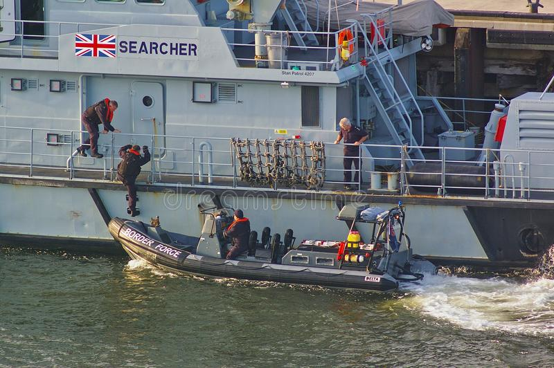 Newcastle, United Kingdom - October 5th, 2014 - UK border force officers boarding a RIB patrol boat alongside the border force cut. Newcastle, United Kingdom royalty free stock photography