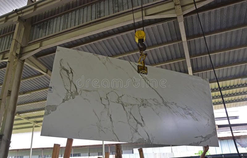 A newly arrived stone slab is being lift to be shown to customer. A newly arrived stone slab is being lift out of the storage in a warehouse to be shown to royalty free stock photo