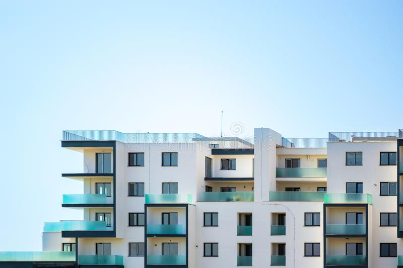 Newly built apartments building on a bright blue sky, with space for text on top. Upper part of a white building. Newly built apartments building on a bright stock photos