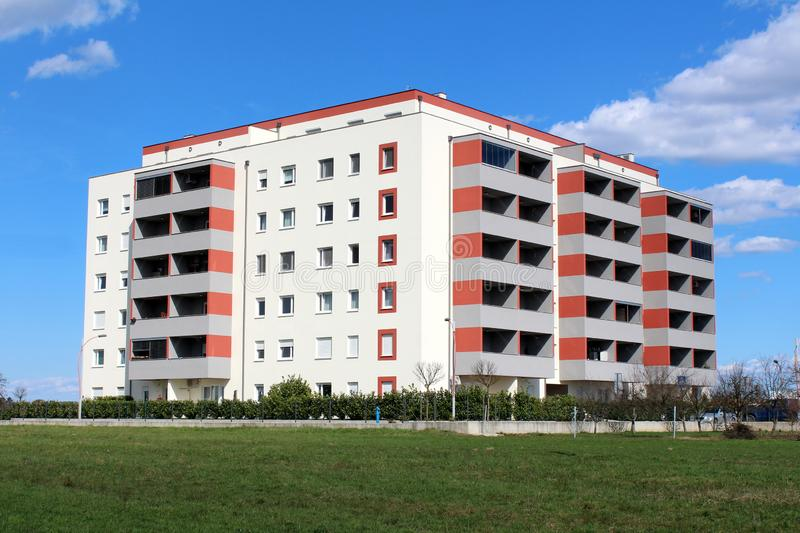 Newly built modern apartment building with multiple apartments and balconies surrounded with grass and small hedge stock images