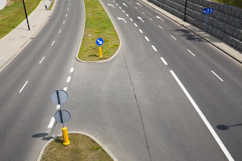 Newly built urban road. A new roadway with designated lanes and road signs defining the direction of traffic royalty free stock photo
