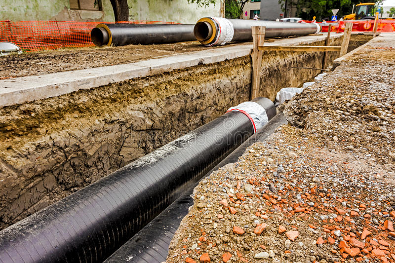 Newly laid pipe in a fresh trench. Unfinished pipeline. New pipeline in the process of building, under construction stock photography