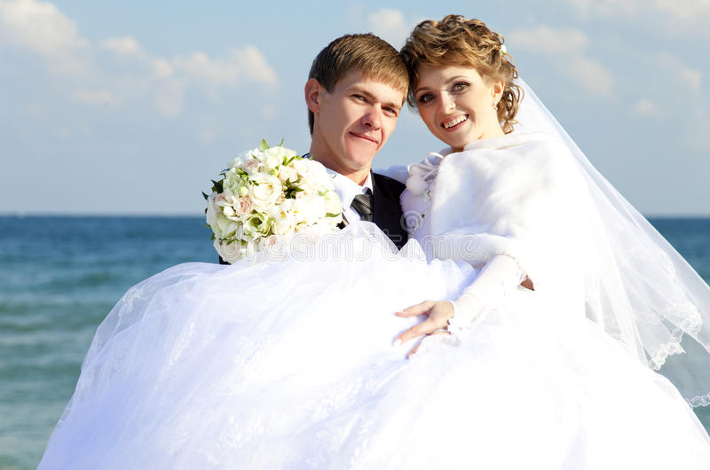 Newly married couple kissing on the beach.